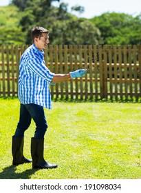 young man spreading lawn fertilizer on his backyard