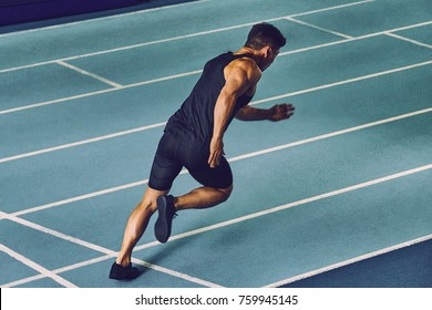 Young man sprinting on a blue indoor racetrack wearing sports clothing & looking tired after a training session.