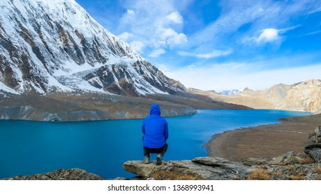 Young man squatting at the rock in front of Tilicho Lake. Blue and calm surface of the lake, mountains covered in the shadow, sunlight in the back. Overcast. Harsh landscape. Thankfulness, freedom.