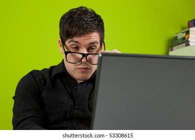 Young man squinting at the laptop