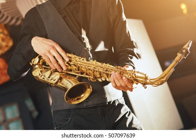 Young man stand with musical instrument saxophone. Musical instrument saxophone for play music jazz. Saxophonist with a saxophone.