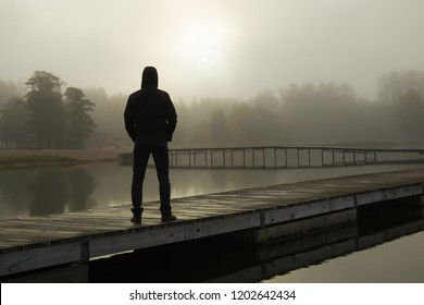 Young man standing alone on lake footbridge and staring at sunrise in gray, cloudy sky. Mist over water. Foggy air. Early chilly morning. Dark, scary moment and gloomy atmosphere. Back view.