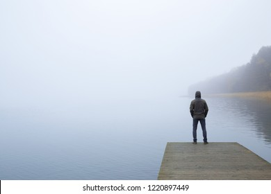 Young man standing alone on edge of footbridge and staring at lake. Mist over water. Foggy air. Early chilly morning in late autumn. Peaceful atmosphere in nature. Back view. Empty place for text.