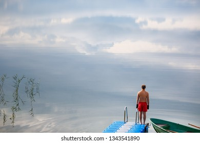 Young man standing alone on the jetty in the lake . Sunrise over the lake in the village. View from a boat bridge