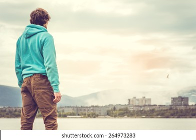 Young Man standing alone outdoor Travel Lifestyle concept with lake and city on background
