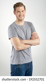 Young man standing with arms folded on light background