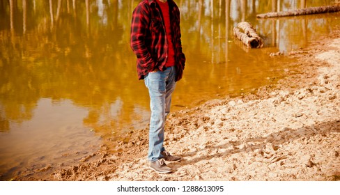 Young man standing around a lake shore area