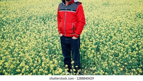 Young man standing around a mustard field wearing red jacket