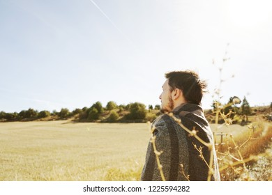 A young man standing from back enjoying in calm the morning autumn sun in a path of a yellow field with the backlight from the blue sky
