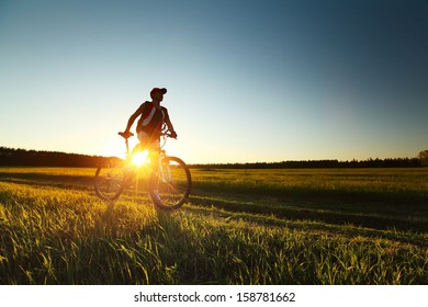 Young man standing with bicycle on a rural road in a green meadow