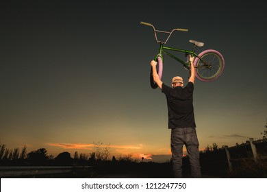 Young man standing bmx bike. BMX rider with and a sunset. Concept urban sports