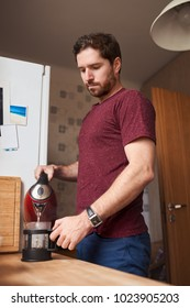 Young man standing by the counter in his kitchen in the morning pouring hot water from a kettle into a coffee press
