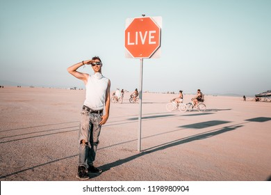 Young man standing by the dream sign in the middle of a desert at the Burning Man art festival. Sign to live your life.