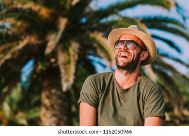Young man standing by the palm trees looking at sun
