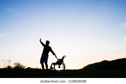 A young man standing by wheelchair in nature in the evening.