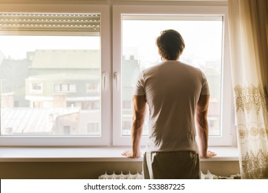 Young man standing by the window in the morning