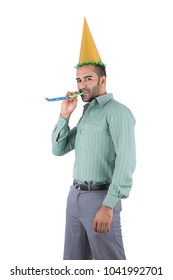 A young man standing in a classic outfit putting a party cone on head and blower on the mouth, isolated on a white background.
