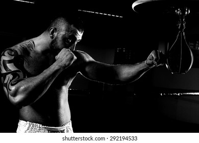 young man standing exercising with boxing bag