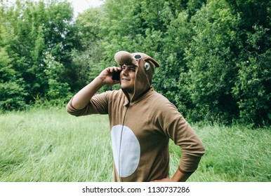 Young man is standing in the forest in cosplay costume of a cow. Guy in the funny animal pyjamas sleepwear is talking on smartphone outdoors. Halloween ideas for party in the nature.