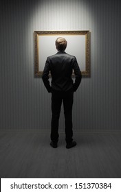 A young man standing in front a empty frame in a museum