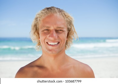 Young man standing in front of the sea while beaming