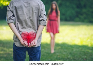 Young man standing in front of a young woman holding a heart behind his back. Saint Valentine's day.