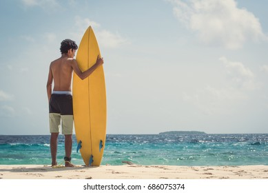 a young man standing with his surfboard at beach