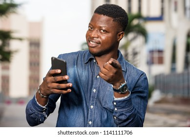 young man standing in jeans with mobile phone looking at camera smiling.