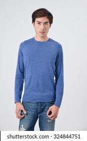 young man standing in jeans posing on white background