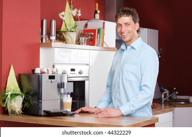 Young man standing in the kitchen beside a coffee machine