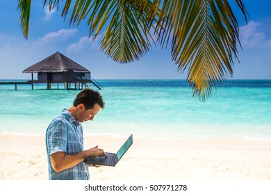 young man standing with laptop and mobile on a wooden bridge near the water bungalows, of background colorful beach of island