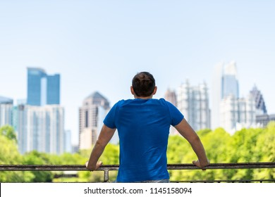 Young man standing leaning on railing in Piedmont Park in Atlanta, Georgia with scenic cityscape skyline of urban city skyscrapers downtown, Lake Clara Meer