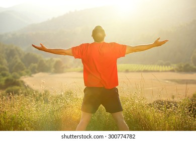 Young man standing in nature with arms outstretched during sunset