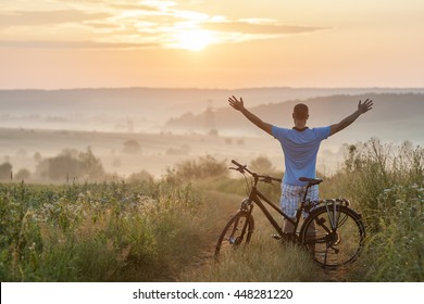 Young man standing near  bicycle in morning sunrise with wonderful rays and morning mist during calm summer active day