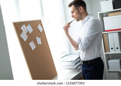 The young man is standing near the board with stickers and raised a pencil to his lips.