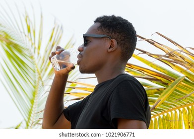 young man standing near coconut palm leaves drinking mineral water in a glass.