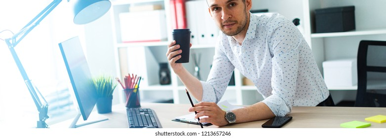 A young man is standing near a table in the office, holding a pencil and a glass of coffee. A young man works with documents and a computer.