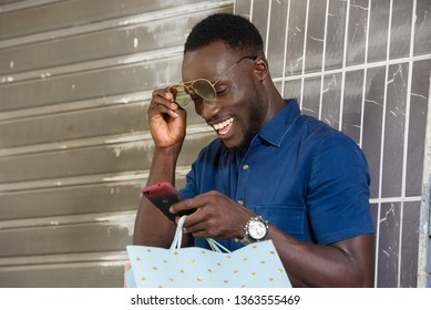 young man standing near a wall after shopping looking at mobile phone while smiling.