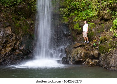 young man standing near a waterfall in the rainforest of Costa Rica