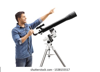 Young man standing next to a telescope and pointing up isolated on white background