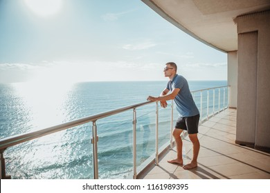 Young man standing on the balcony looking at the sea. Relaxation minute concept