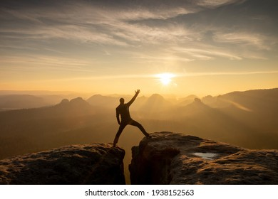 Young man standing on a cliff edge celebrates reaching the top of the mountain, arms in the air, shouting.