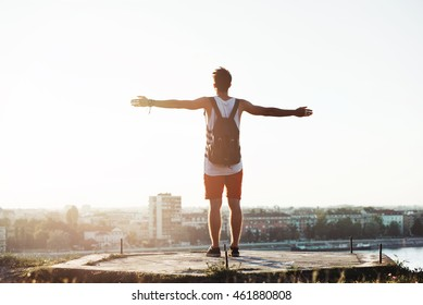 Young man standing on the cliff with a city view, arms wide open