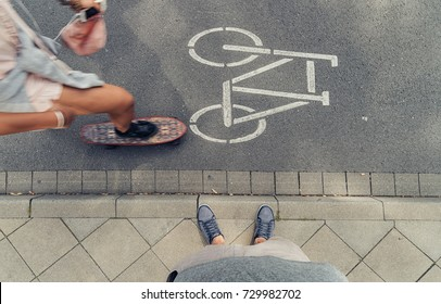 Young man standing on a curbside in the city and a woman drives with a Mini Cruiser Board on the streets. Point of view shot.