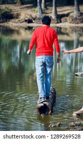 Young man standing on a dead tree parts in the water