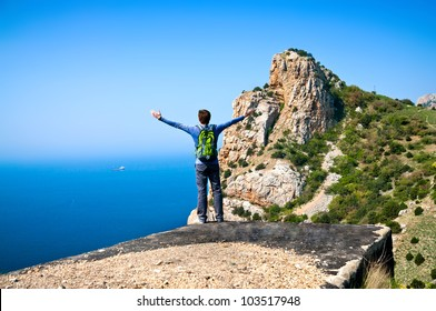a young man standing on a hill and watching the beautiful scenery