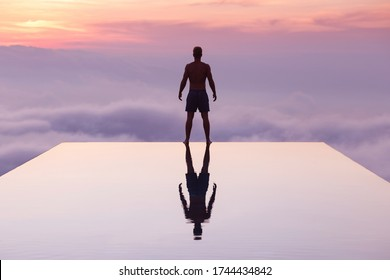 A young man standing on an infinity pool during sunset time. The pool was located high in elevation, so he felt like swimming into the clouds. Bali. Handsome young man. Fit. Reflection.