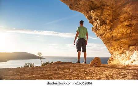 Young man standing on a ledge in Cave Calypso, as he watches the  sunset (Gozo Island, Malta)