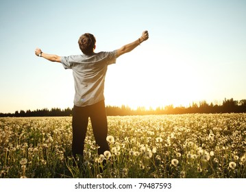 Young man standing on a meadow with dandelions on a blue sky background