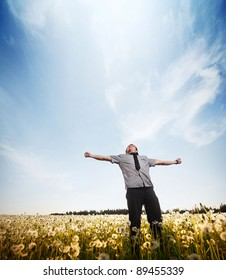 Young man standing on a meadow with raised hands